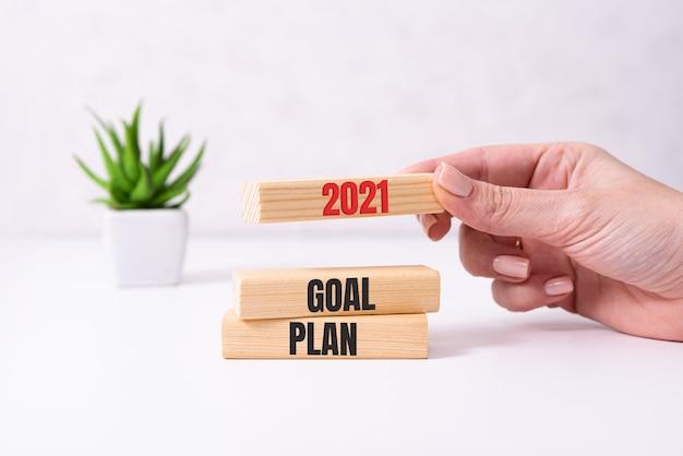 테이블에 텍스트 2021 목표, 계획 및 조치와 나무 큐브를 들고 사업가 손