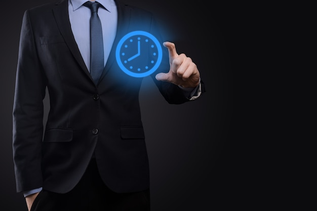 Businessman hand holds the icon of hours clock with arrow.