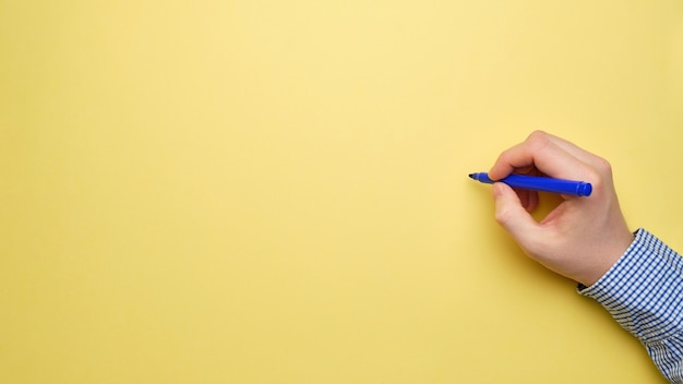 Businessman hand holds a pencil on a yellow sheet of paper with a top view and copy space.
