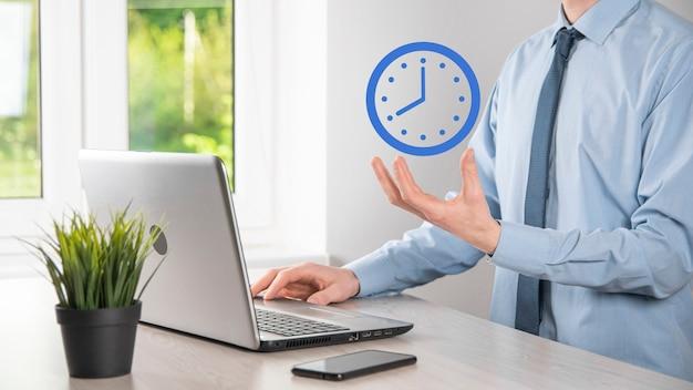 Рука бизнесмена держит значок часов часов со стрелкой. оперативное выполнение работы. бизнес-тайм-менеджмент и бизнес-время - деньги концепции