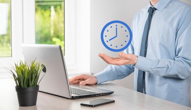 ビジネスマンの手は、矢印の付いた時間時計のアイコンを保持します。仕事の迅速な実行。ビジネス時間管理とビジネス時間はお金の概念です。