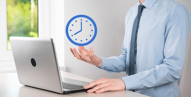 ビジネスマンの手は矢印の付いた時間時計のアイコンを保持します。仕事の迅速な実行。ビジネス時間
