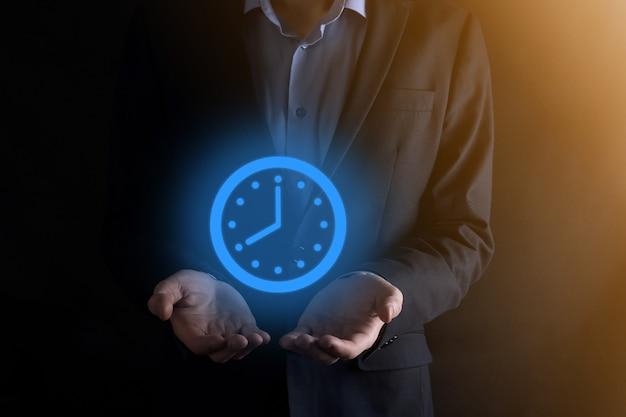 ビジネスマンの手は矢印と時間時計のアイコンを保持します