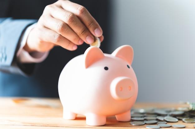 ビジネスのために貯金箱にコインを挿入し、お金を節約するビジネスマンの手
