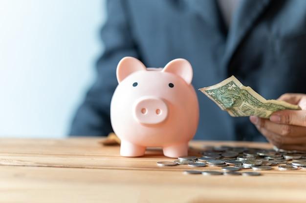 사업을 위해 돼지 저금통에 동전을 삽입하고 돈을 저축하는 사업가 손