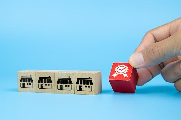 Рука бизнесмена выбирает блог деревянных игрушек куба со значком качества из магазина значков франчайзингового маркетинга