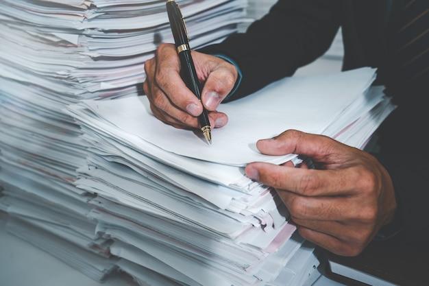 ビジネスマンの手は紙の上に置き、ペンで番号を書く