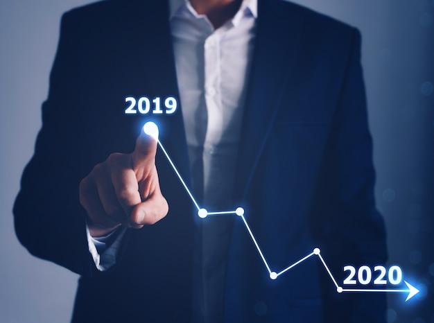 Рука бизнесмена делая диаграмму уменьшения. концепция экономического спада в 2020 году по сравнению с 2019 годом. мировой финансовый кризис в 2020 году.