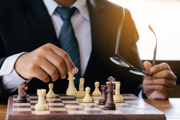 Businessman hand moving chess figure in competition success play.