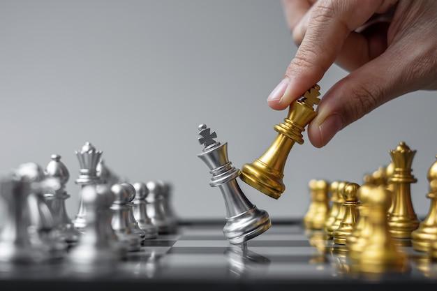 골드 체스 킹 그림 및 장군 적 또는 체스 판 경쟁 동안 상대를 이동하는 사업가 손.