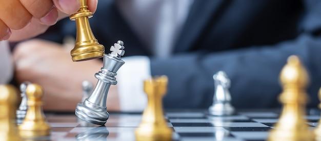 チェス盤の競争中に金のチェスキングフィギュアとチェックメイトのエネルギーまたは対戦相手を動かすビジネスマンの手。