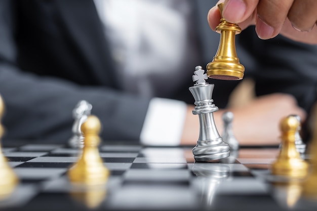 Businessman hand moving gold chess king figure and checkmate enermy or opponent during chessboard competition.