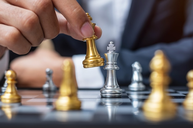 Businessman hand moving gold chess king figure during chessboard competition.