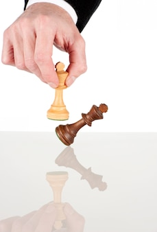 Businessman hand moving the king to win