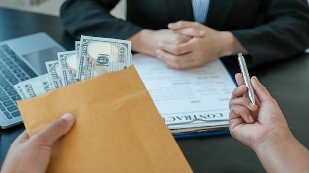 Рука бизнесмена предлагает взятки деньги в конверте для подписания контракта о бизнесе.