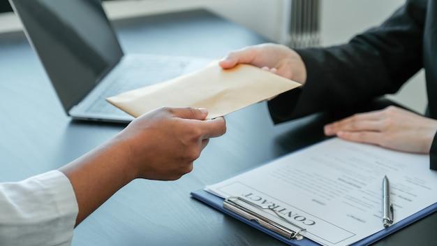 Рука бизнесмена предлагает взятки деньги в конверте для подписания контракта.