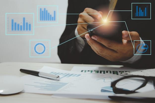 Бизнесмен рука телефон цифровой график и диаграмма. анализ бизнес-документов и отчет с ручкой на столе.