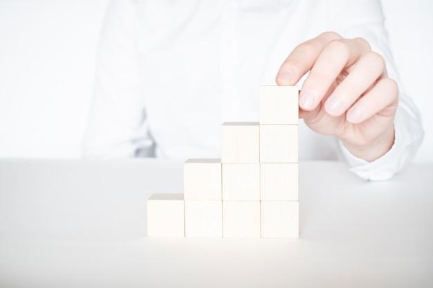 Рука бизнесмена размещение или потянув красный деревянный блок на здании. бизнес-планирование, управление рисками, решение, стратегия, разные и уникальные концепции
