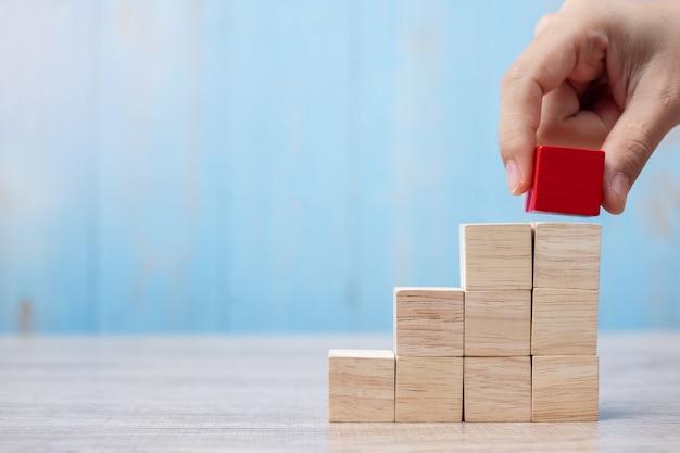 사업가 손 배치 또는 건물에 빨간 나무 블록을 당겨.