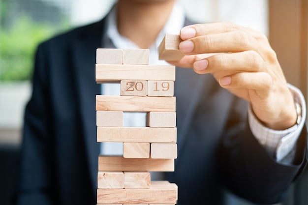 Businessman hand placing or pulling wooden block on the tower