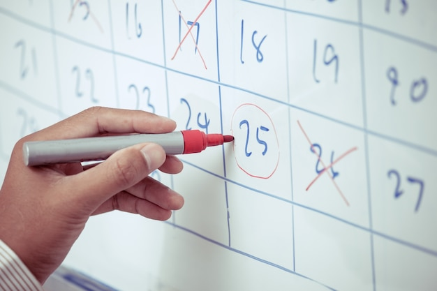 Businessman hand planning his schedule on the whiteboard Premium Photo
