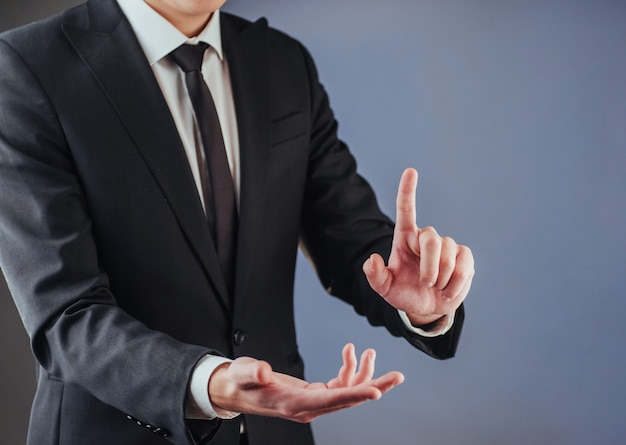Businessman hand pointing on empty space on black background