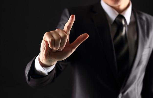 ビジネスマンの手が仮想画面上の架空のボタンを押す
