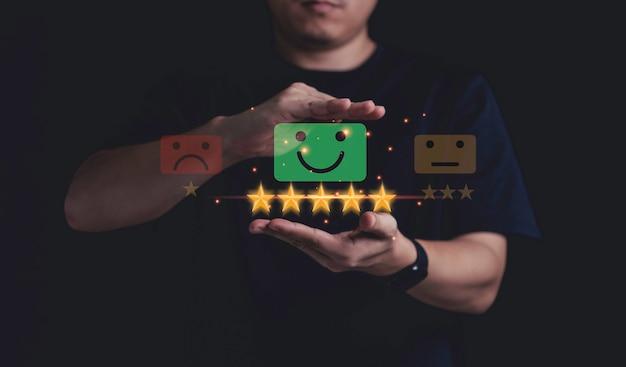 사업가의 손은 파란색 빛나는 빛, 고객 평가, 제품 및 서비스 개념에 대한 고객 만족도로 5개의 노란색 별을 보호합니다.