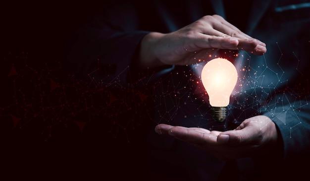 창의적인 사고 아이디어와 혁신 개념을 위한 연결선으로 빛나는 전구를 보호하는 사업가입니다.