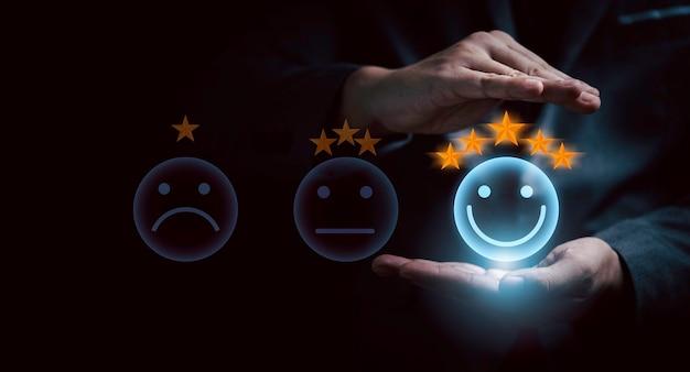 사업가는 최고의 평가를 위해 미소 버튼을 보호하고 고객의 우수한 평가, 고객 만족도 개념을 보호합니다.