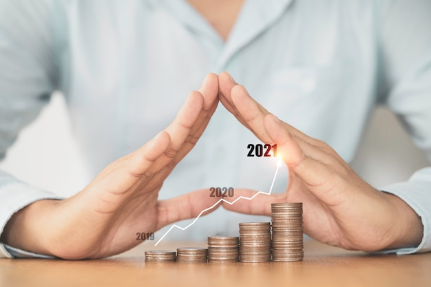 Businessman hand protecting stacking coins with virtual graph , business investment profit and saving growth in 2021 concept.