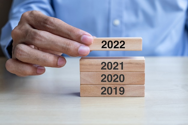 테이블 배경에 2022 나무 빌딩 블록을 당기는 사업가 손. 사업 계획, 위험 관리, 해결, 전략, 솔루션, 목표, 새해 new you 및 해피 홀리데이 개념