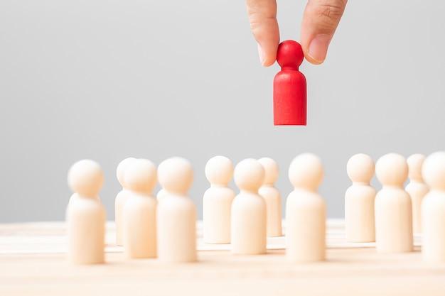 Рука бизнесмена тянет человека лидера деревянного от толпы сотрудников. токсичные люди, управление человеческими ресурсами, подбор персонала, работа в команде и концепции лидерства