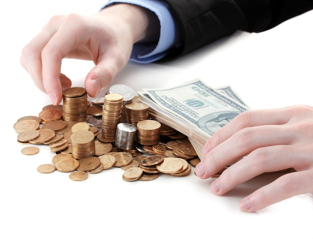 ビジネスマンの手は白で隔離のコインを置きます