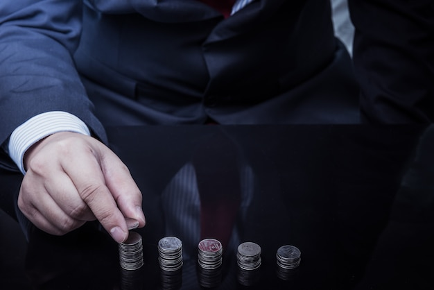 Businessman hand put coins to stack of coins
