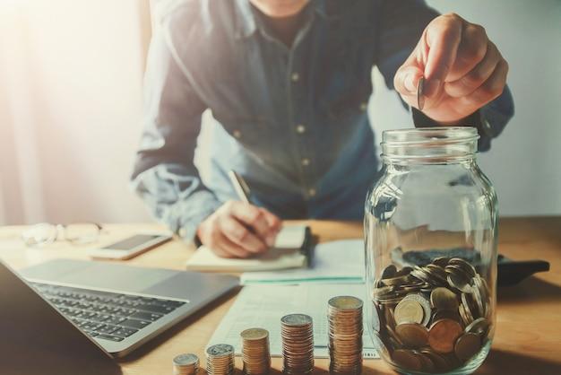 Businessman hand puting coins into jug glass