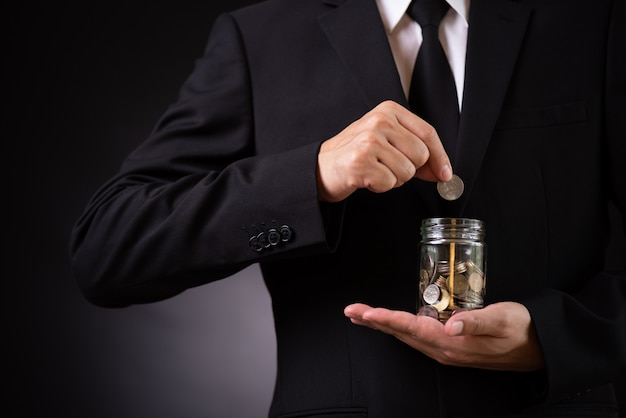 Businessman hand putting coin into jar. finance savings, investment concept