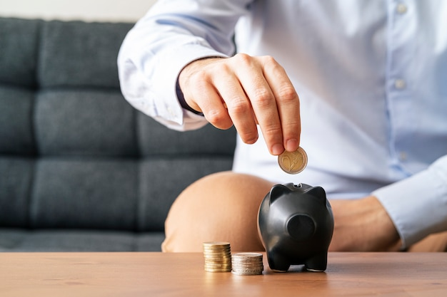 Businessman hand putting coin into piggy bank. saving money concept