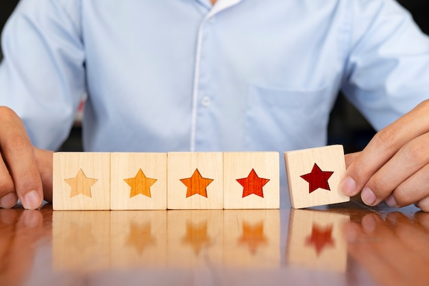 Businessman hand putting wooden five star shape on table.