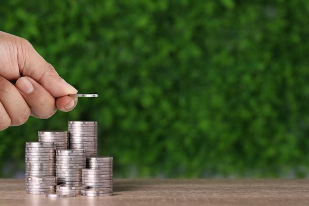 Рука бизнесмена укладывая монету, растущую на деревянном столе и зеленом фоне природы.