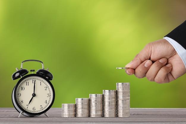 나무 테이블과 녹색 자연에 알람 시계와 함께 성장하는 사업가 손 스태킹 동전