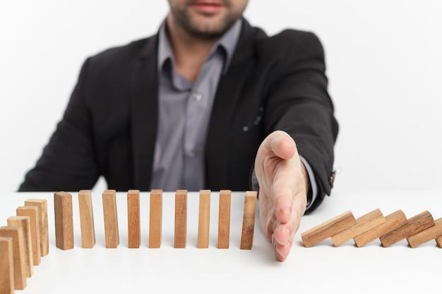 사업가 손 중지 도미노 연속 팁 또는 위험. 사업 전략.