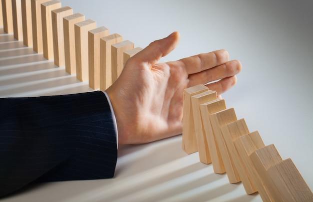 Бизнесмен рука перестает падать куски домино