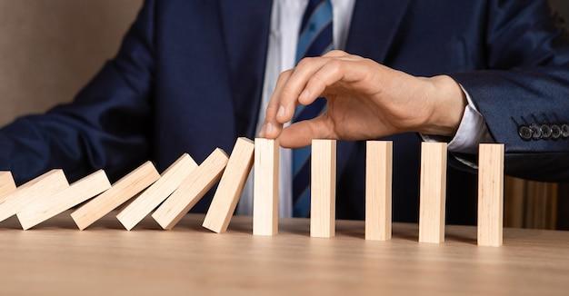 Рука бизнесмена останавливает падающий деревянный эффект домино от непрерывного свержения или риска, стратегии и концепции успешного вмешательства для бизнеса.