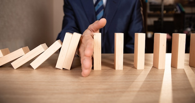 Businessman hand stopping falling wooden dominoes effect from continuous toppled or risk, strategy and successful intervention concept for business.