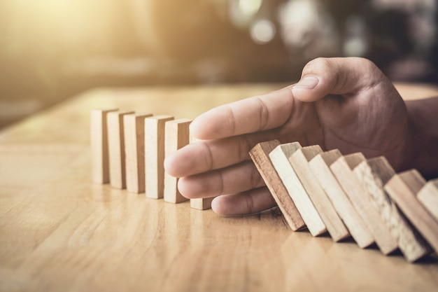 Businessman hand stopping falling wooden dominoes effect from continuous toppled