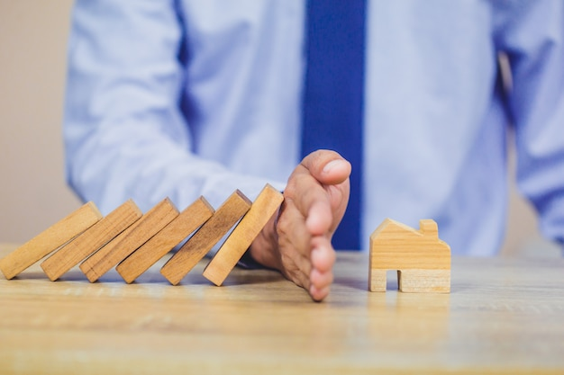 Businessman hand stopping risk the wooden blocks from falling on house.