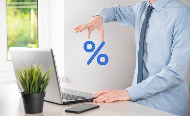 ビジネスマンの手は、パーセント記号のアイコンを取ります。金利金融および住宅ローン金利の概念。