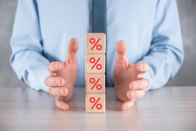 Рука бизнесмена берет деревянный кубик, изображающий, показанный значок символа процента. концепция финансовых и ипотечных ставок процентной ставки.