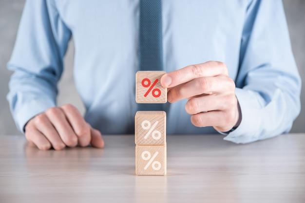 Рука бизнесмена берет деревянный кубик, изображающий, показанный значок символа процента.